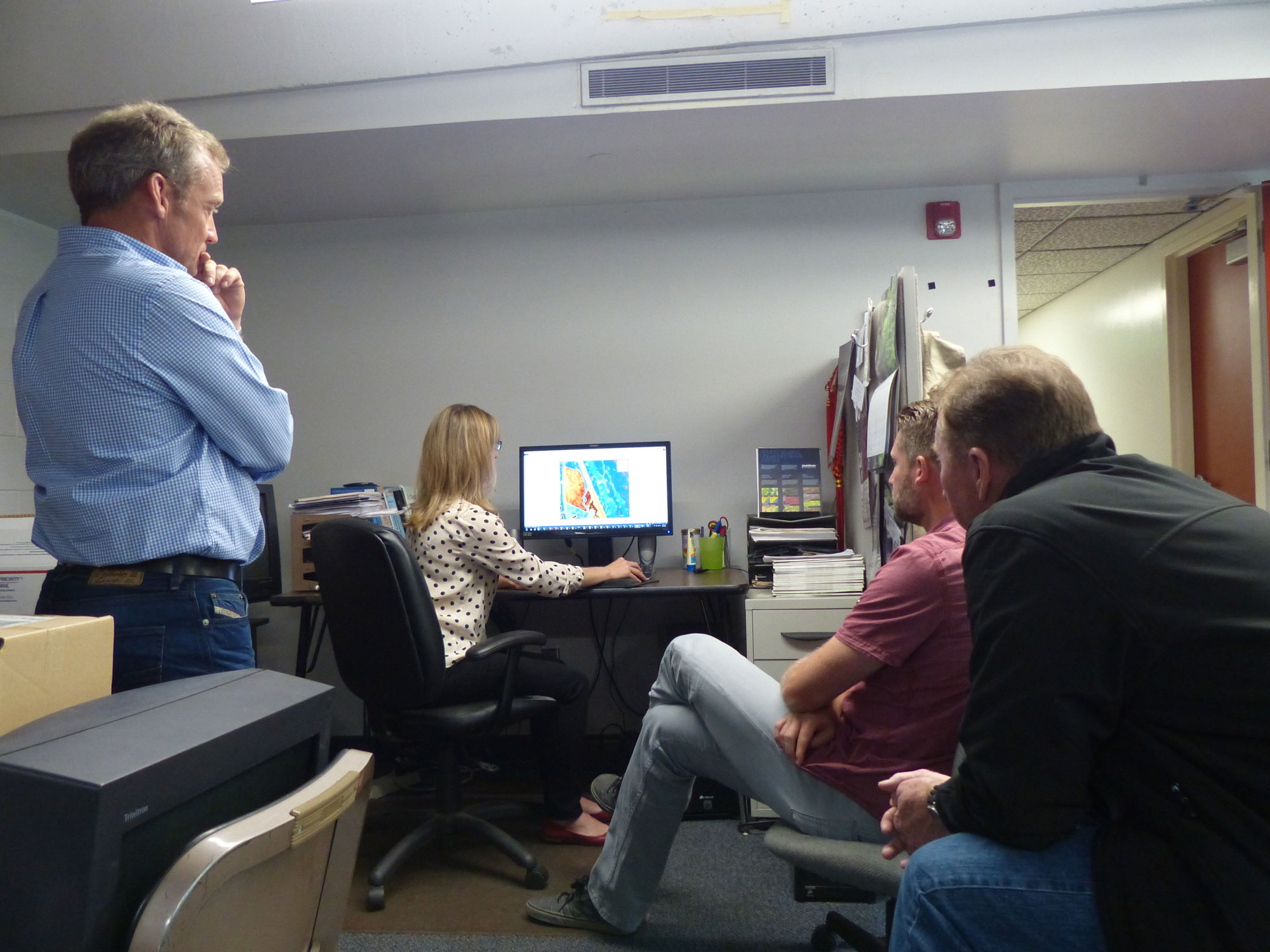 People in room looking at computer with processed information
