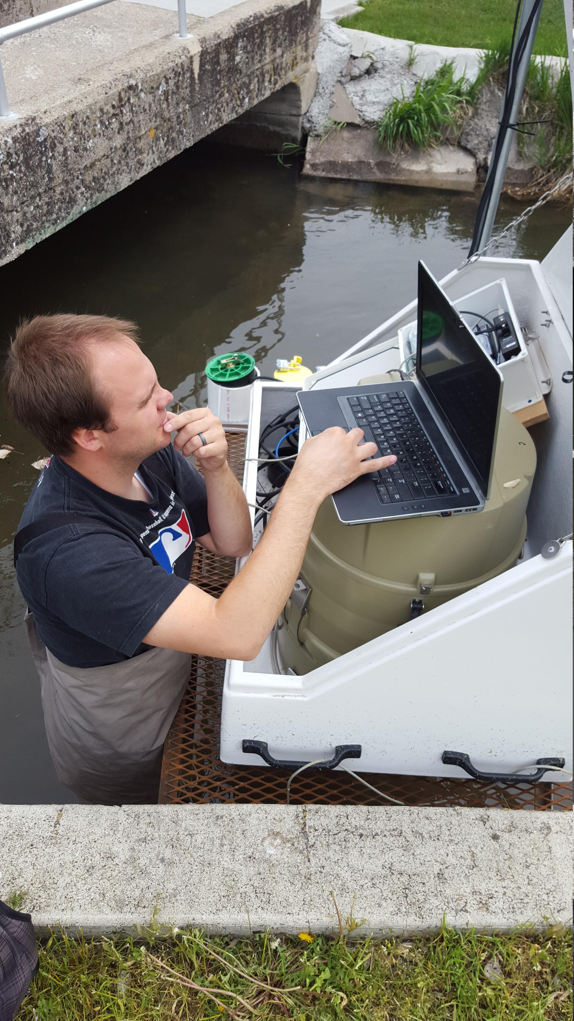 Person in canal working on laptop on bank